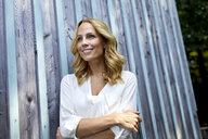 Smiling blond woman in front of wooden wall - PNEF01020