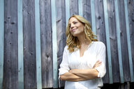Smiling blond woman in front of wooden wall - PNEF01023