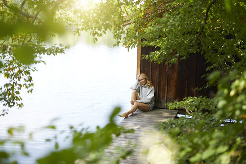 Relaxed woman sitting on wooden jetty at a remote lake - PNEF01026