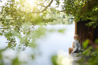 Relaxed woman sitting on wooden jetty at a remote lake - PNEF01032