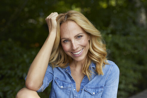 Portrait of smiling blond woman outdoors - PNEF01038