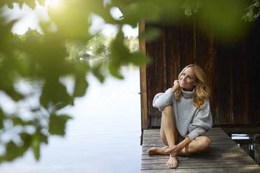 Smiling relaxed woman sitting on wooden jetty at a remote lake - PNEF01047
