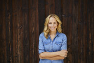 Portrait of smiling blond woman in front of wooden wall - PNEF01050