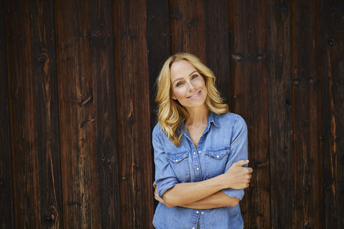 Portrait of smiling blond woman in front of wooden wall - PNEF01053