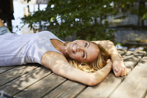 Happy blond woman lying on wooden jetty at a lake - PNEF01056