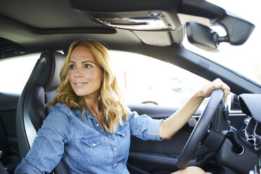 Smiling woman driving car - PNEF01059