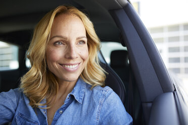 Portrait of smiling woman driving car looking out of window - PNEF01065