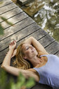 Smiling blond woman lying on wooden jetty at a lake - PNEF01068