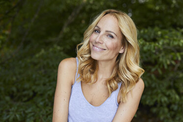 Portrait of smiling blond woman outdoors - PNEF01071