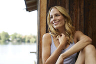 Smiling blond woman in front of wooden hut - PNEF01074