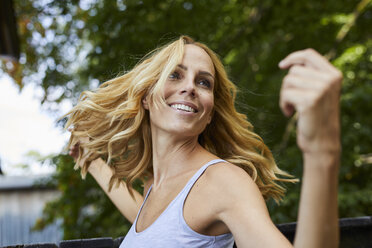 Carefree blond woman outdoors - PNEF01077