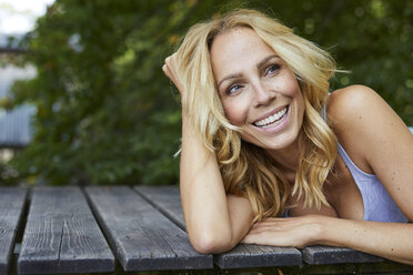 Portrait of happy blond woman lying on wooden jetty - PNEF01080
