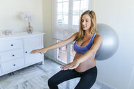 Pregnant woman practicing with fitness ball - KIJF02031