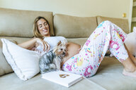 Pregnant woman and dog lying on the couch at home - KIJF02055