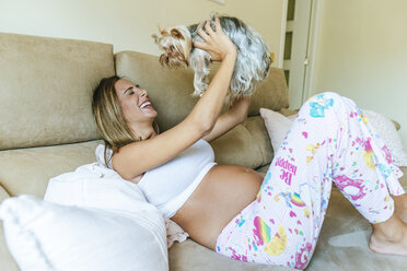 Happy pregnant woman playing with her dog on the couch at home - KIJF02058