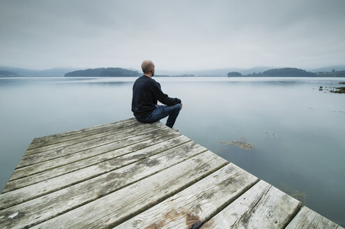 Lonely man sitting on jetty looking at distance - RAEF02179