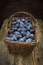 Wicker basket of organic plums, wooden table - LVF07461