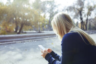 Blond woman using smartphone in autumnal city park - AZF00097