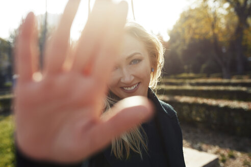 Portrait of smiling blond woman raising her hand in a park - AZF00103