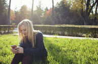 Smiling blond woman sitting on a meadow in autumnal city park using smartphone - AZF00106