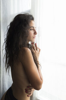 Young shirtless woman standing at the window watching something - JPTF00024