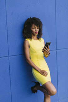 Portrait of fashionable businesswoman leaning against blue wall looking at cell phone - FMGF00065