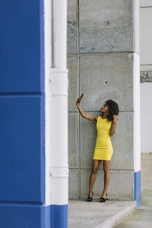 Fashionable businesswoman in yellow dress taking selfie with smartphone - FMGF00068
