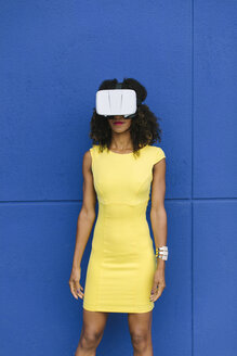 Woman in yellow dress wearing Virtual Reality Glasses against blue background - FMGF00071