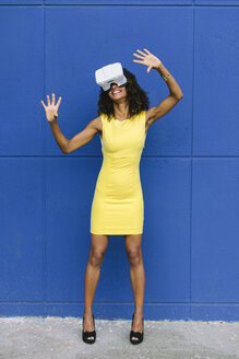 Woman in yellow dress using Virtual Reality Glasses against blue background - FMGF00074