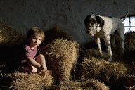 Portrait cute girl with dog sitting in hay - FSIF03327