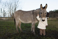 Girl petting donkey in rural field - FSIF03339
