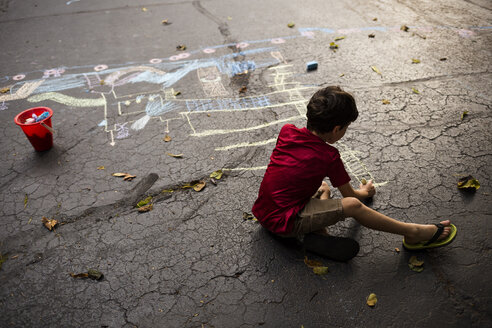 Full length of playful boy drawing with chalk on asphalt during autumn - CAVF49127