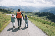 Rear view of mother with daughters walking on mountain road against cloudy sky - CAVF49139