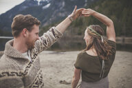 Happy young couple dancing on lakeshore at Silver Lake Provincial Park - CAVF49154