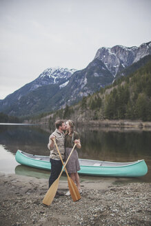 Young couple holding oars while kissing on lakeshore at Silver Lake Provincial Park - CAVF49157