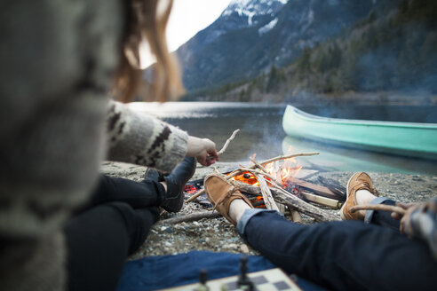 Low section of couple sitting by burning campfire at Silver Lake Provincial Park - CAVF49160