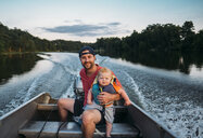 Portrait of father with son sitting in motorboat on lake - CAVF49181