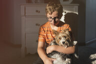 Boy holding Yorkshire Terrier while sitting at home - CAVF49205