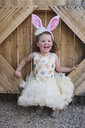 Happy girl wearing costume while standing by wooden fence - CAVF49217