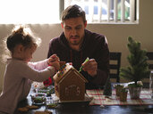 Daughter with father decorating gingerbread house on table at home - CAVF49220