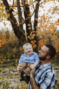 Father carrying son while standing in forest during autumn - CAVF49229