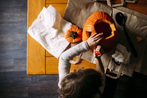 Overhead view of girl making jack o' lantern on table at home - CAVF49247