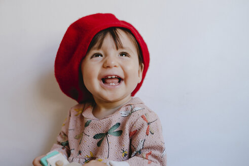 Cheerful baby girl looking up against wall at home - CAVF49268