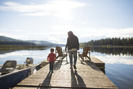Rear view of mother and son walking on wooden pier over lake against sky - CAVF49277