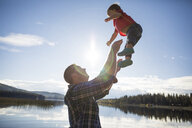 Side view of playful father throwing son in air against lake and sky during sunny day - CAVF49280