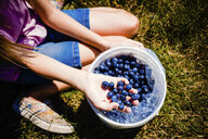 Low section of girl with blueberries in bucket sitting on field at farm - CAVF49298