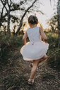 Rear view of girl dancing on field against sky at park during sunset - CAVF49310