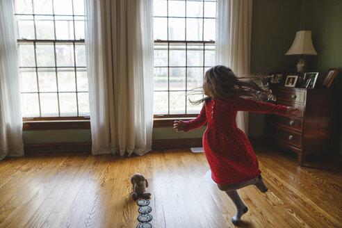 Full length of girl spinning while dancing on hardwood floor at home - CAVF49316