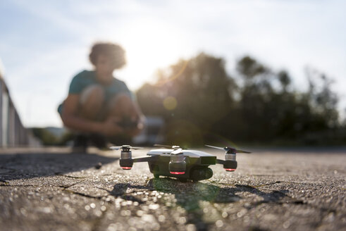 Boy landing his drone on the street - DIGF05143