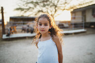 Portrait of girl standing at farm during sunset - CAVF49365